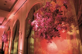 pink-flowers-hung-on-wall-next-to-tall-window-with-drapery