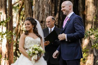 bride-and-groom-smile-at-guests-with-pastor-at-wedding