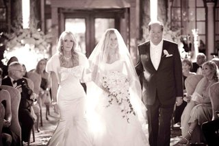 black-and-white-photo-of-bride-escorted-down-aisle-by-mom-and-dad