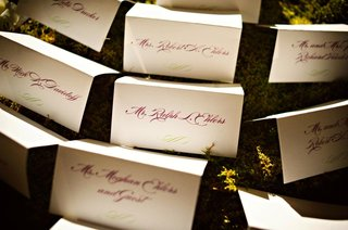 wedding-reception-place-cards-arranged-on-greenery