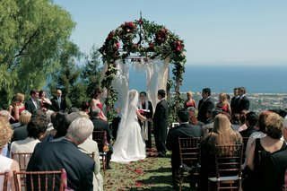 ceremony-structure-covered-with-flowers-and-organza