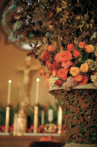 wedding-ceremony-arrangement-of-orange-yellow-and-green-flowers-with-branches-of-dry-leaves