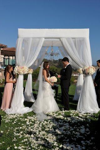 bride-and-groom-at-oceanfront-ceremony-under-chandelier