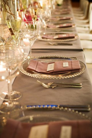 wedding-reception-place-setting-with-a-clear-beaded-charger-and-pink-napkin