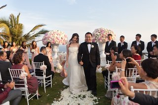 bride-and-groom-hold-hands-up-rose-petal-aisle