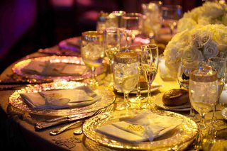 wedding-reception-place-settings-with-gold-rimmed-glassware-and-chargers