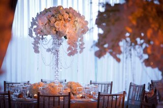 wedding-reception-centerpiece-of-white-flowers-in-a-tall-crystal-candelabra-draped-with-crystals