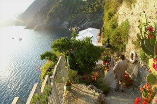 bride-and-groom-walk-down-steps-of-cinque-terre-cliff