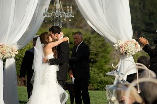 newlyweds-kiss-under-white-chuppah-and-chandelier