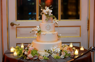 white-cake-with-white-flowers-and-gold-monogram