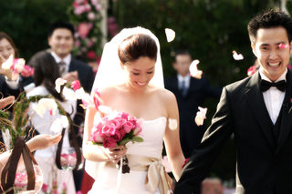 groom-and-bride-carrying-pink-bouquet-walk-up-the-aisle