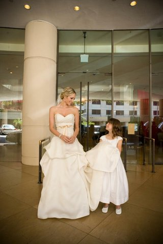 young-girl-holding-up-train-of-bridal-gown