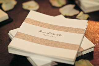 off-white-cocktail-napkin-with-bride-and-grooms-names-wedding-date-and-decorative-tan-bands