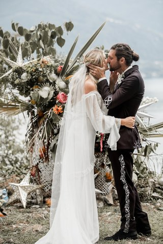 bride-in-daughters-of-simone-wedding-dress-kiss-groom-man-bun-at-boho-ceremony-lake-como