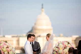 bride-and-groom-rooftop-wedding-ceremony-altar-officiant-exchange-vows-united-states-capitol