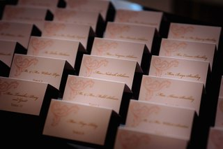 pink-design-on-escort-card-with-gold-script-names-and-table-numbers