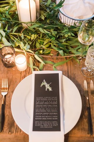 wood-table-greenery-with-black-menu-card-leaf-monogram-on-top-white-plate-wood-table-black-gold-fork