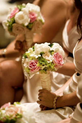 bridesmaids-sitting-at-ceremony-holding-flowers