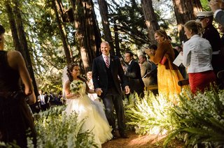 bride-and-groom-walk-through-forest-aisle-at-ceremony