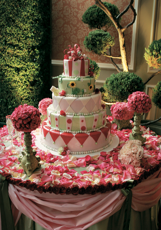 unique-wedding-cake-on-table-covered-with-rose-petals