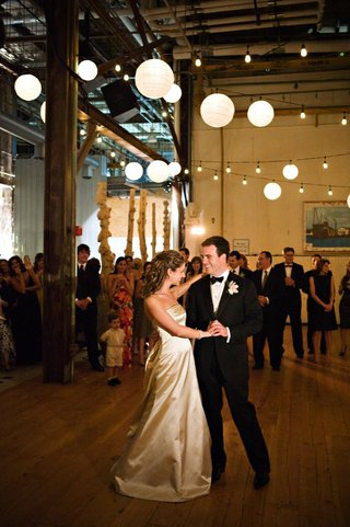 bride-in-a-strapless-monique-lhuillier-gown-dances-with-groom-in-a-tuxedo