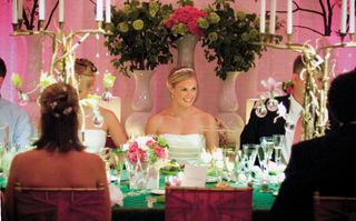 bride-sits-at-table-decorated-with-green-linens-and-candelabras-made-of-branches
