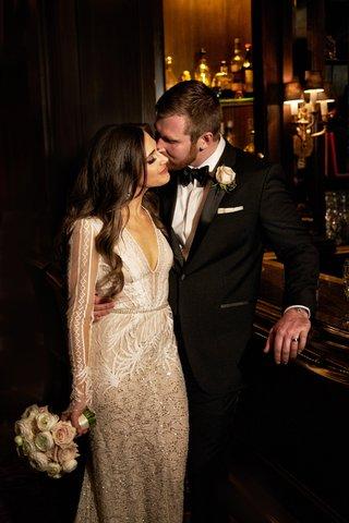 bride-in-long-sleeve-inbal-dror-wedding-dress-with-groom-in-tuxedo-bow-tie-with-long-brunette-hair