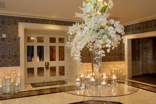 white-flower-arrangement-on-glass-table-outside-of-reception