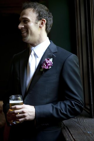 groom-in-black-suit-and-white-tie-with-beer