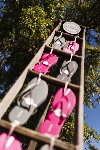 pink-and-grey-flip-flops-on-rustic-ladder-at-reception