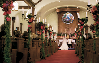 wedding-ceremony-aisle-decorated-with-tall-candelabra-covered-in-greenery-and-topped-with-flowers