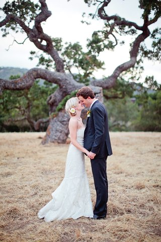 bride-and-groom-holding-hands-in-front-of-tree