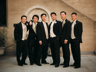 groom-and-groomsmen-in-black-tuxedos-with-cream-vests-and-ties