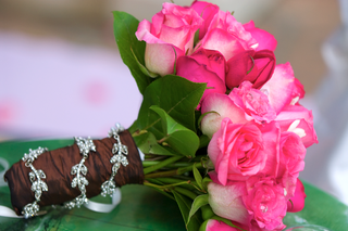 hot-pink-roses-and-green-leaves-tied-with-brown-ribbon