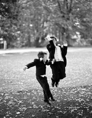 black-and-white-photo-of-ring-bearers-jumping