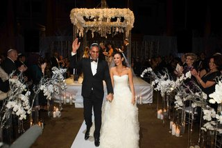 bride-and-groom-walk-up-white-aisle-with-winter-flower-arrangements
