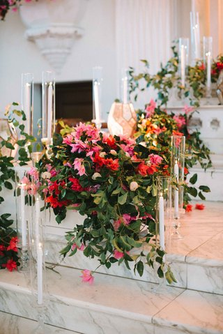 cascading-bold-florals-ceremony-altar-marble-steps-glass-votives