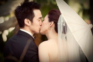 bride-and-groom-kiss-under-umbrella