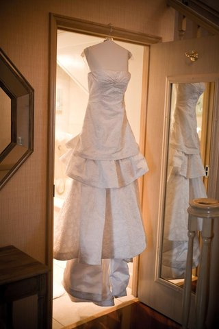 tiered-carolina-herrera-wedding-dress-on-hanger