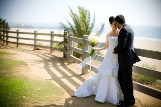 bride-and-groom-on-pathway-by-beach