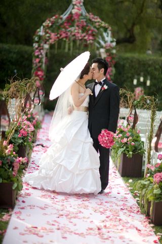 bride-carrying-parasol-kisses-groom-on-pink-petal-aisle
