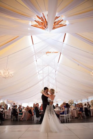 bride-and-groom-dance-under-draped-reception-tent