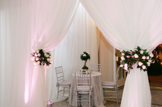 table-with-silver-linens-and-chairs-if-framed-by-white-draping-tied-with-red-and-white-flowers