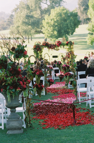 rose-petals-on-grass-aisle-flanked-by-greenery