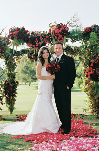 bride-and-groom-standing-on-rose-petals