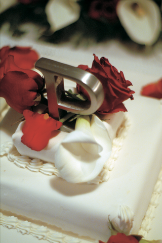 white-cake-with-metal-silver-letter-on-top-with-red-roses