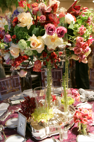 centerpiece-of-colorful-flowers-in-a-candelabra-surrounded-by-small-bouquets