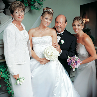 bride-smiles-with-mother-of-the-bride-father-and-sister