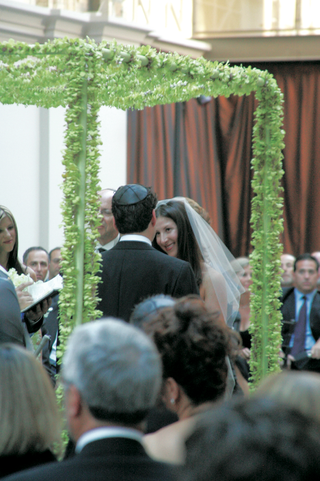 bride-and-groom-under-chuppah-of-green-dendrobium-orchids