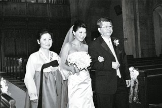 black-and-white-photo-of-bride-walking-down-the-aisle-with-parents